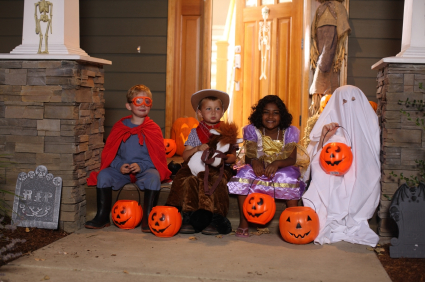 Children dressed in halloween costumes sitting on a porch with candy buckets