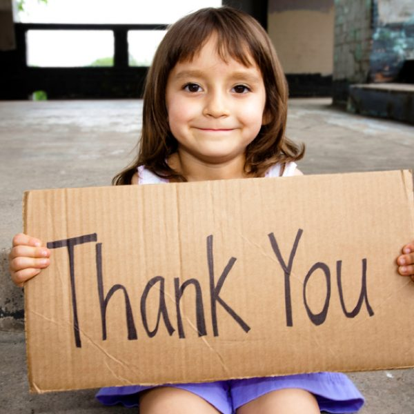 Little girl holding a cardboard sign that says thank you
