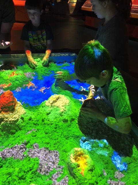 Children playing at a kinetic sand table