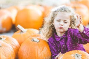 Little girl in a pumpkin patch bliwing a kiss