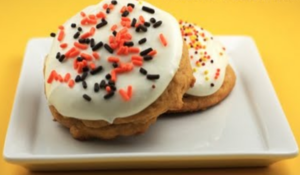 Pumpkin cookies with cream cheese icing, fall colored sprinkles on a white plate
