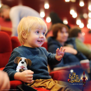 Little boy with stuffed dog watching elf on the shelf the musical