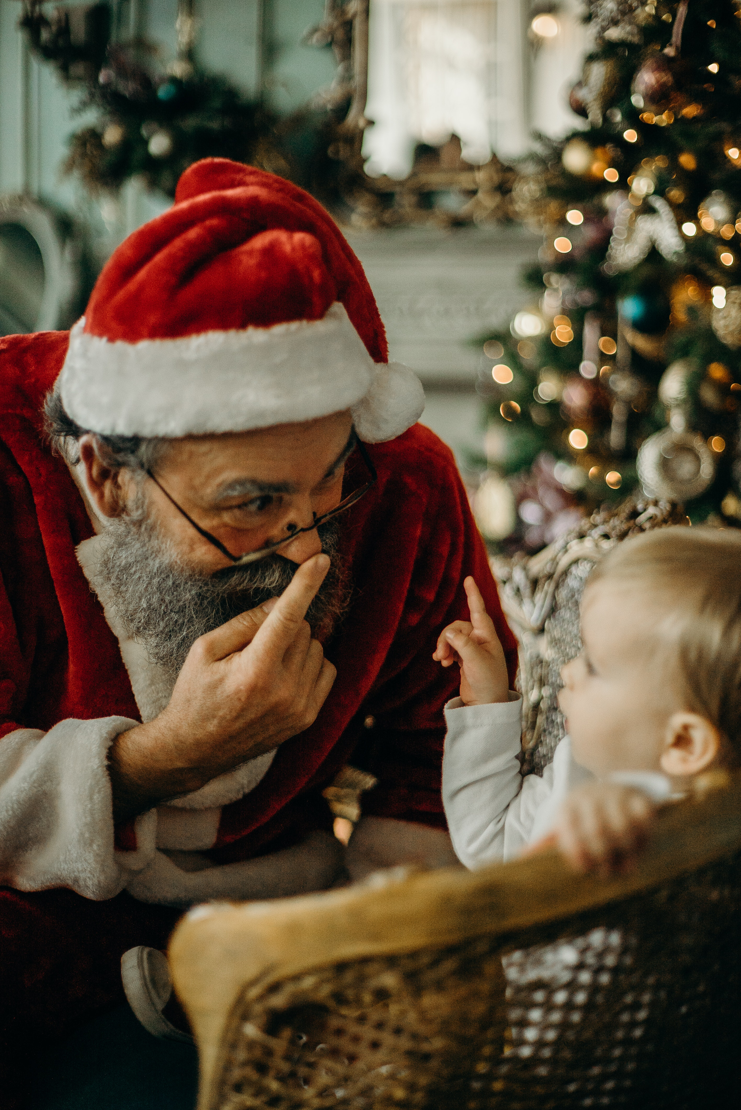 Santa claus pointing at his nose looking at a baby