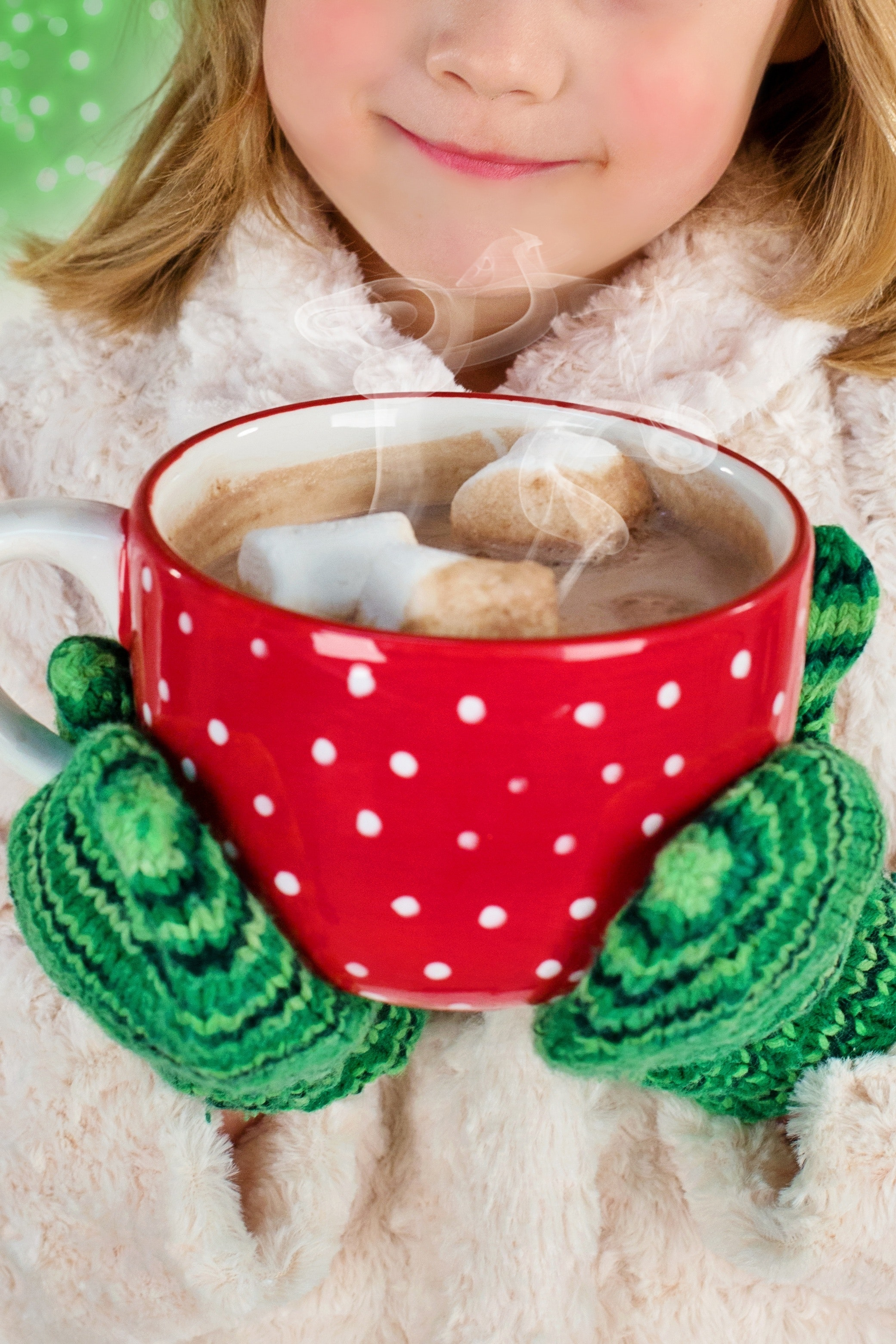 Girl in white coat holding a red mug of hot cocoa with marshmallows