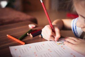 Little girl holding pencil doing school work